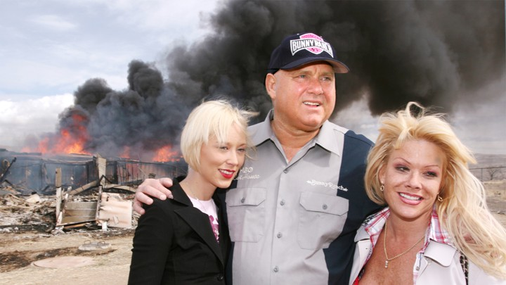 Dennis Hof poses with two blond women as a building burns.