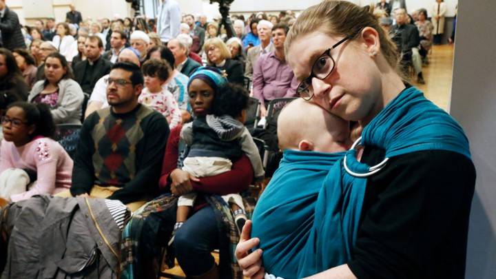 A woman holds her baby at a Pittsburgh memorial service at Temple Emanuel in Roanoke, Virginia.
