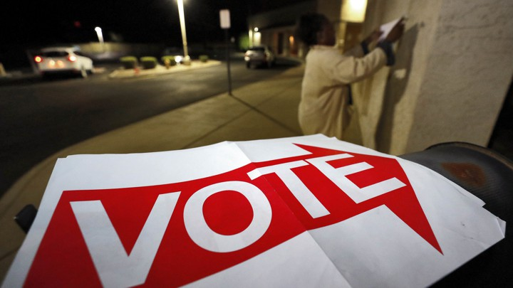 "An election official hangs ""Vote"" signs outside a polling station in Phoenix, Arizona."