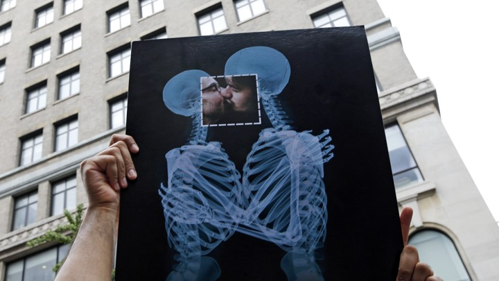 A couple kisses behind an X-ray poster.
