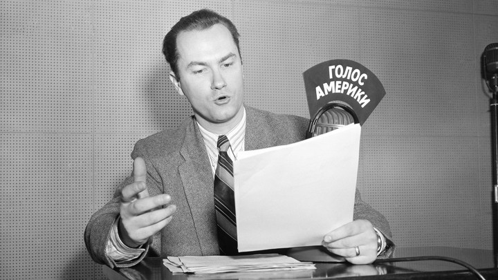 A black-and-white photo of a man reading and speaking into a radio microphone labeled in Russian