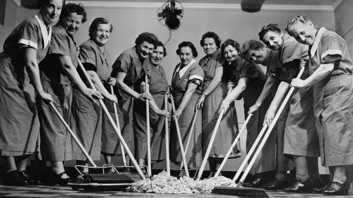 Women in maid uniforms smile at the camera while pushing mops.