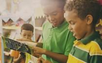 Young children perusing books at a Scholastic book fair