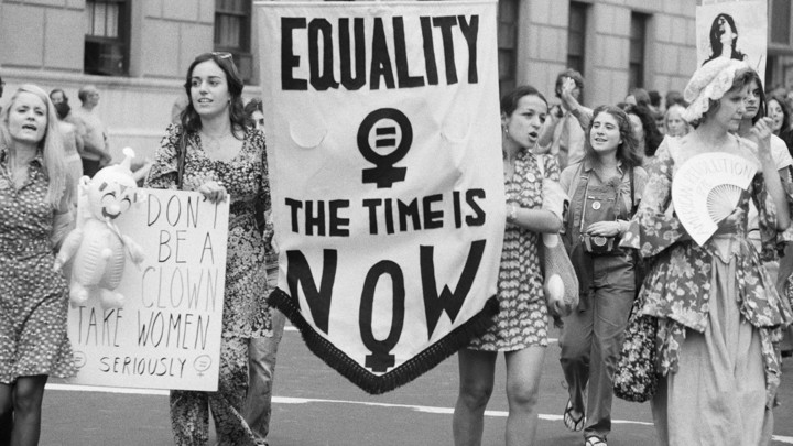 "Women carry a sign reading ""Equality: The Time Is Now"" at a women's liberation parade."