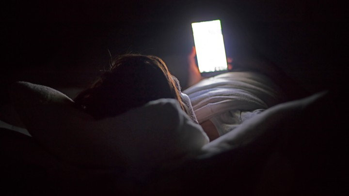 A woman looks at her phone in the dark