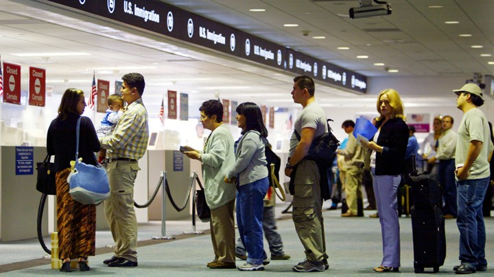 Visitors arriving at the Miami airport wait in line to have their passports checked.