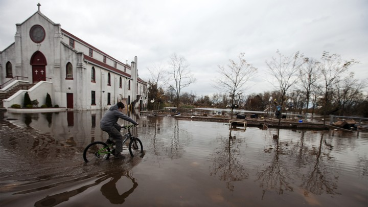 A person rides a bicycle past a church on a flooded street.