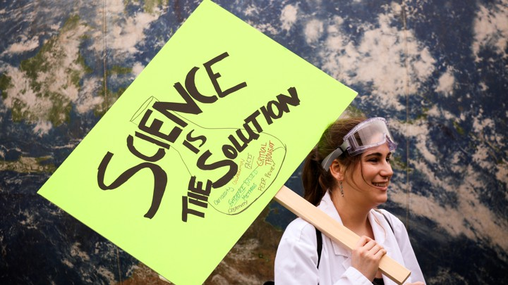 A female protester in a lab coat holds a sign saying: 'Science Is the Solution'