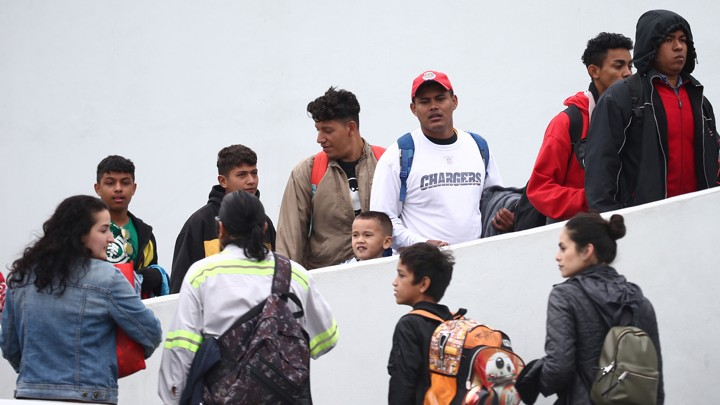 Members of a caravan of migrants enter the U.S. Customs and Border Protection facility where they are expected to apply for asylum, in Tijuana, Mexico, on May 2, 2018.