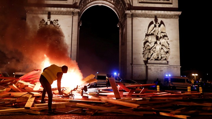 A protester wearing a yellow vest burns a barricade in front of a stone arch.