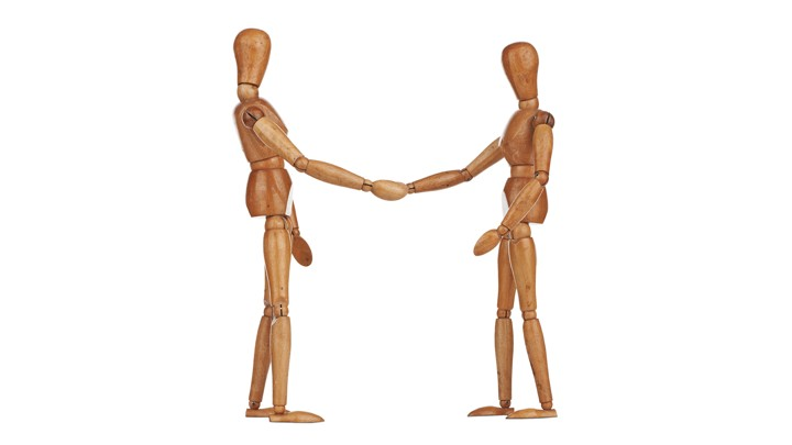 Two stick-figure wooden models shake hands.