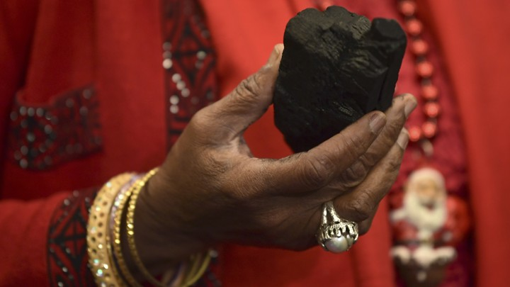 A woman holds a lump of coal