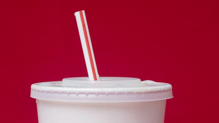 A paper cup with a plastic lid and straw