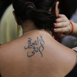 A person holds their hair up to reveal a tattoo in Arabic on their upper back.