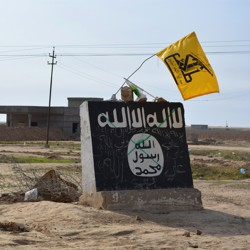 A flag of the Shiite militant group Saraya al-Khorasani flutters over a mural depicting the emblem of the Islamic State in Al-Alam, a village in Iraq.