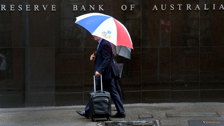 Two men walk past the Reserve Bank of Australia