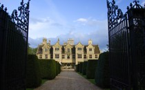 A picture of a large estate behind a set of gates