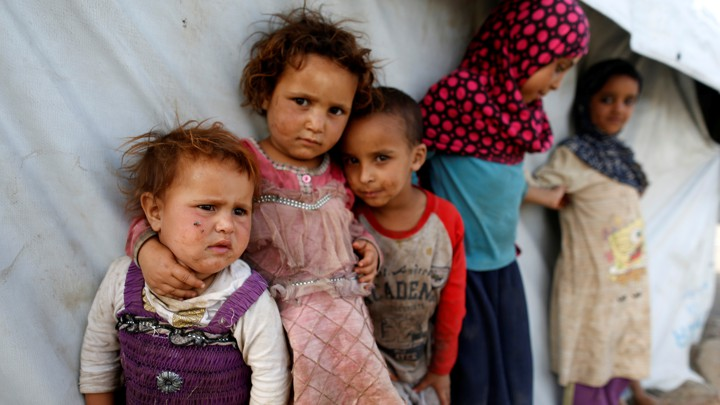 Children stand next to a tent at a camp for people displaced by the war near Sanaa, Yemen.