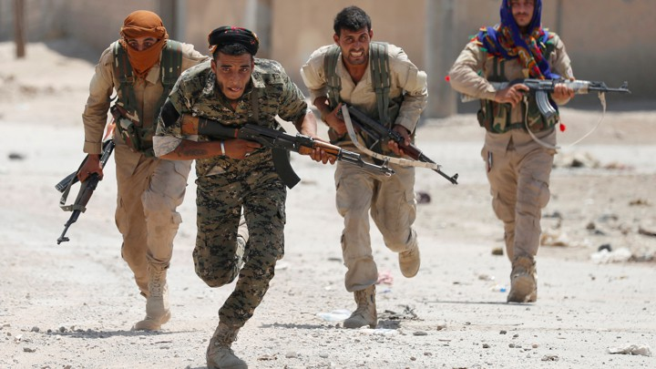 YPG fighters run through the streets of Raqqa, in Syria.