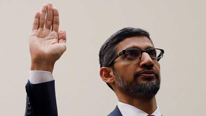 Sundar Pichai raises his right hand.