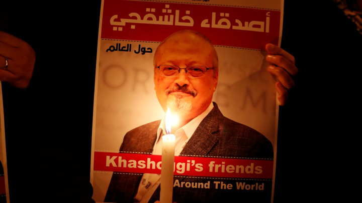 A demonstrator holds a poster with a picture of Jamal Khashoggi.