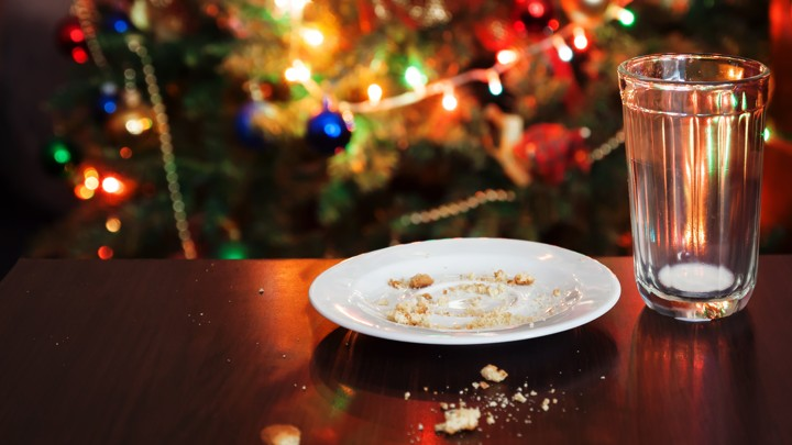 An empty glass of milk and a plate of cookie crumbs sit in front of a Christmas tree
