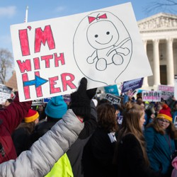 "A person holds a sign saying ""I'm With Her"" with a drawing of a fetus on it."