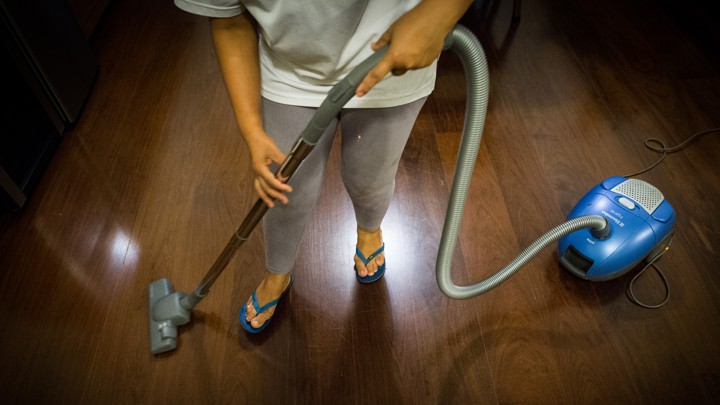 A person vacuums a hardwood floor.