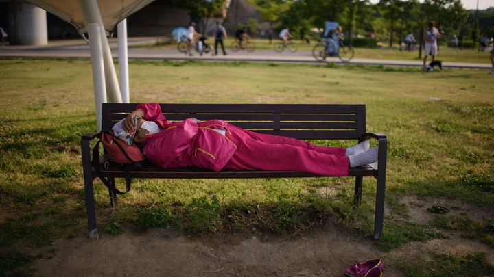 A woman wearing a face mask sleeps on a bench in Seoul.