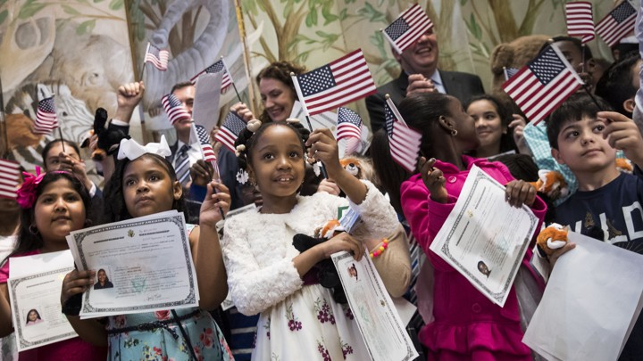 Children waving American flags and holding citizenship certificates