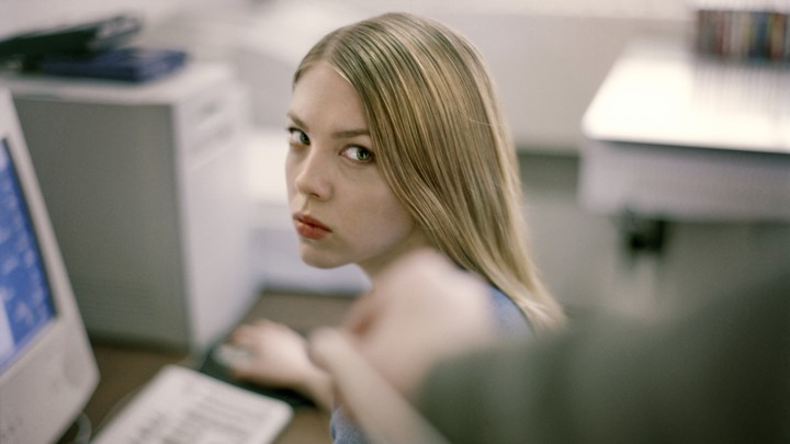 A woman in an office stares angrily at a colleague