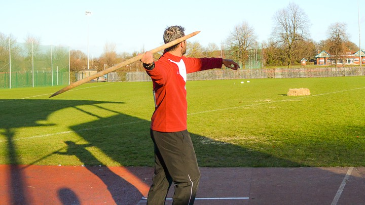 A javelin athlete throwing a replica Neanderthal spear