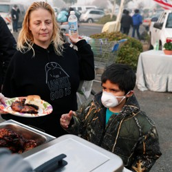 After losing their home in Magalia in the Camp Fire, Robin Tompkins and her son, Lukas, line up for a free meal in a makeshift evacuation center in Chico, California on November 16, 2018