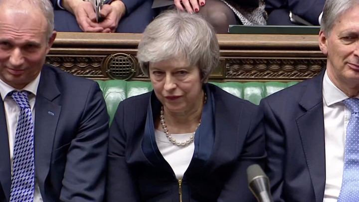 Theresa May sits in Parliament after the body overwhelmingly voted down her Brexit plan.