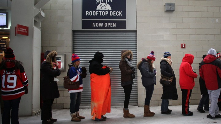 Women wait in a long line for a restroom at a sports stadium.