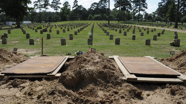Empty graves at the front of a cemetery