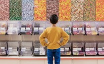 A young boy faces a wall of candy dispensers.