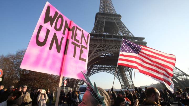 "Protesters attend the Women's March in Paris in 2017. One holds an American flag and one holds a sign that reads ""Women unite."""