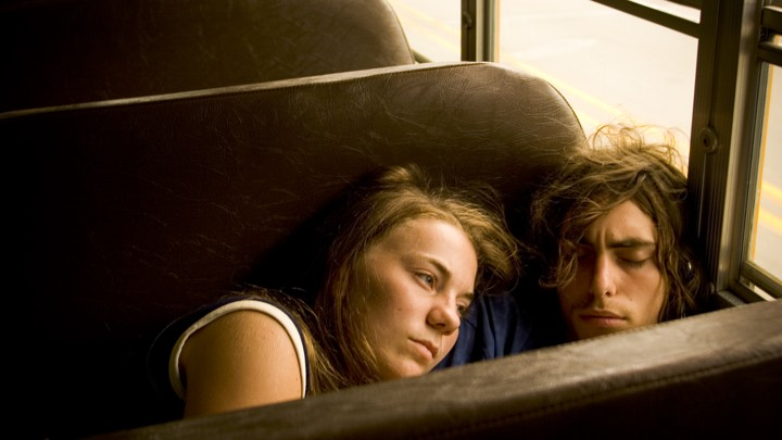 Two teens cuddle on a bus