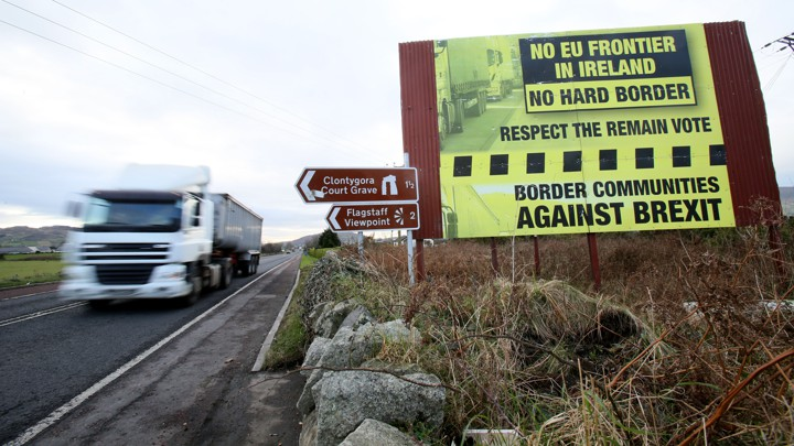 "A truck crosses from the Republic of Ireland into Northern Ireland, past a sign that reads, ""Border communities against Brexit."""