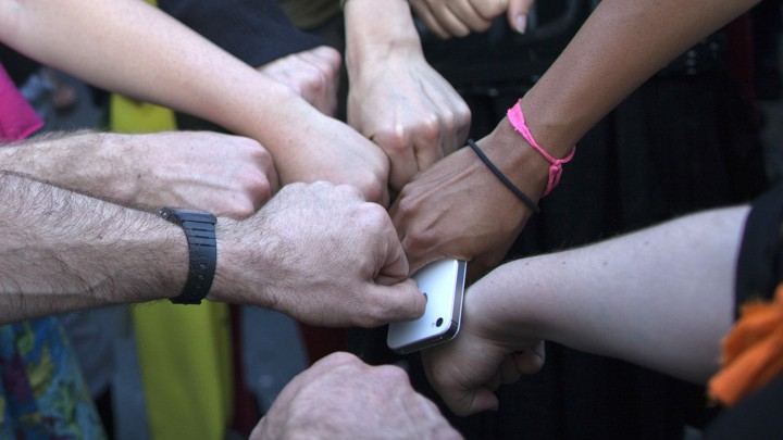 Activists join fists in solidarity ahead of a protest march, with one holding an iPhone