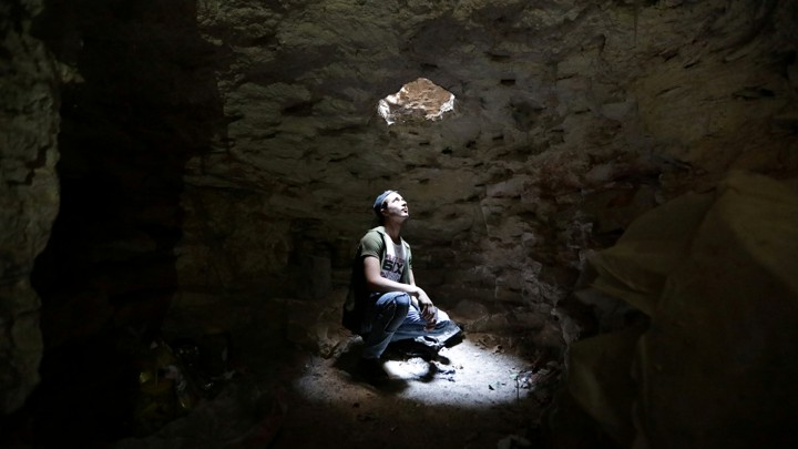 A man looks up through a hole at the top of a cave.
