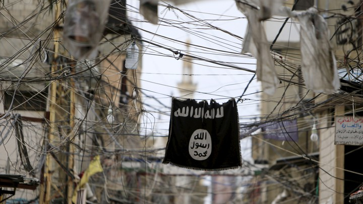 An Islamic State flag hangs amid electrical wires over a street in Lebanon.