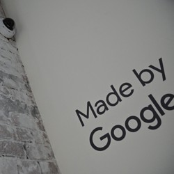 """A security camera on a white brick wall next to a sign that says """"Made by Google"""""""