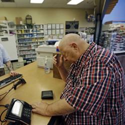 A man picks up prescriptions at a pharmacy.
