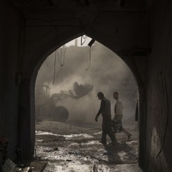 Construction workers remove debris from destroyed shops in Mosul in November 2017.