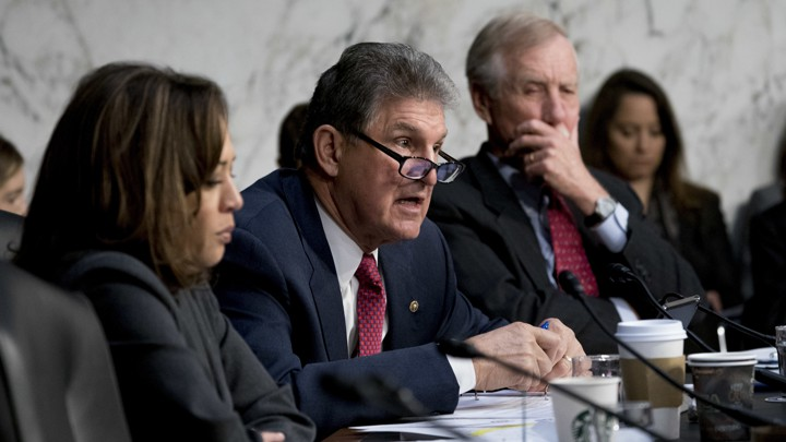 Senator Joe Manchin of West Virginia asks a question at a March 2018 Senate committee meeting. He is flanked by Senator Kamala Harris of California and Senator Angus King of Maine.