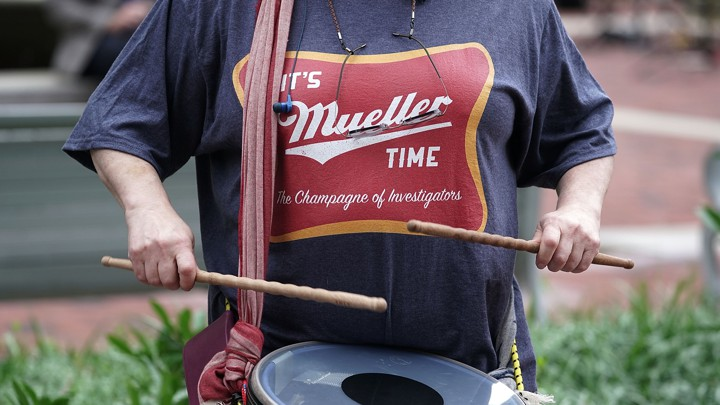 A man beats a drum in a Mueller T-shirt