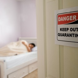 A door with a quarantine sign on it open to reveal a person in bed