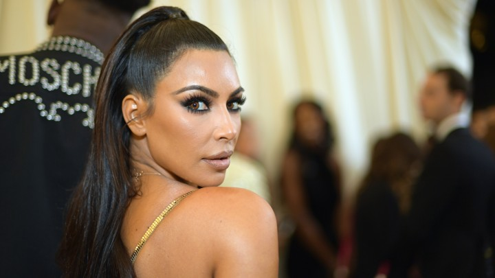 Kim Kardashian looks over her shoulder at the camera.